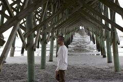 Folly Beach South Carolina, February 17, 2018 - white male walking under beach pier stock photography