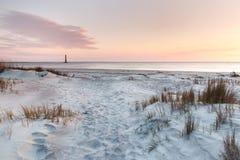 Folly Beach Sunrise Morris Island Lighthouse Charleston SC. Beach landscape of sand, dunes, grasses at sunrise on Folly Beach near Morris Island Lighthouse Stock Photos