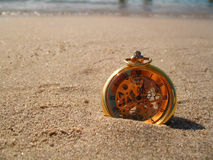 Folowing of time. A closeup of a clock on a beach royalty free stock photo