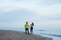 Folâtrez les couples marchant le long de la plage se reposant après séance d'entraînement Images stock