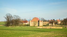 Folwark, a small castle with a moat and a pond. Poland, Folwark, a small castle with a moat and a pond europe old tower village buildings houses field trees royalty free stock photos