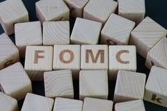 FOMC, Federaal Open Marktcomité concept, kubeert houten blok met alfabet bouwend het woordeof op het centrum op dark stock afbeelding