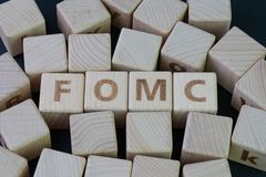 FOMC, Federal Open Market Committee concept, cube wooden block with alphabet building the word FED at the center on dark. Blackboard background, the institution stock image