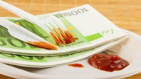 A fome para o dinheiro, os 100 guardanapo dos euro, a ketchup, a forquilha plástica e a faca Imagens de Stock