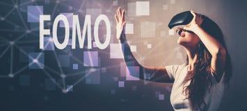 FOMO при женщина используя шлемофон виртуальной реальности стоковая фотография rf