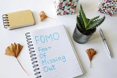 FOMO strach chybianie za pisać w notatniku obraz stock