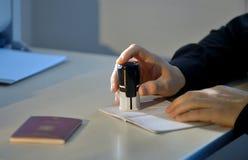 Fonctionnaire des douanes Stamping un passeport photos libres de droits