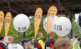 Fonctionnaires aidant des coureurs visant pendant des heures de 3h15 Image stock