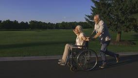 Fonctionnement âgé d'homme tout en poussant l'épouse dans le fauteuil roulant banque de vidéos