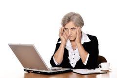 fonctionnement aîné d'ordinateur portatif de femme d'affaires Photographie stock libre de droits