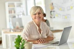 fonctionnement aîné d'ordinateur portatif de femme d'affaires Images stock