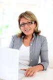 fonctionnement aîné d'ordinateur portatif de femme d'affaires Photo stock