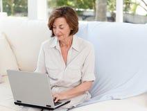 Fonctionnement aîné sur son ordinateur portatif Photos libres de droits
