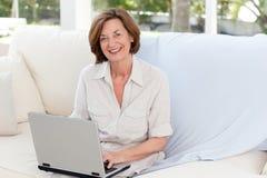 Fonctionnement aîné sur son ordinateur portatif Images libres de droits
