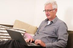 Fonctionnement aîné sur un ordinateur portatif Images libres de droits