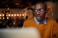 Fonctionnement africain d'homme avec l'ordinateur portable en café images libres de droits