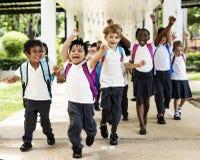 Fonctionnement d'étudiants de jardin d'enfants gai après classe Images stock