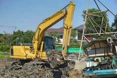 Fonctionnement d'excavatrice de Makro pour ajuster la surface au chantier de construction camion de travail de makro de contrôle  Photo libre de droits