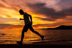 Fonctionnement d'homme à l'île et à lui courant près de la plage avec le coucher du soleil et le beau ciel avec le nuage gentil image libre de droits