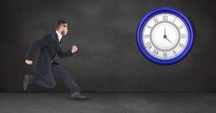 Fonctionnement d'homme d'affaires tout en regardant l'horloge Image libre de droits