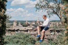 Fonctionnement d'homme situé sur un mur en pierre Images libres de droits