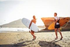 Fonctionnement de couples de surfers ainsi que des planches de surf sur la plage au coucher du soleil - amis sportifs ayant l'amu images stock
