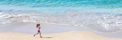 Fonctionnement de coureur par l'océan sur la plage photographie stock libre de droits