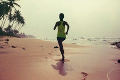 Fonctionnement de femme sur la plage tropicale pendant le lever de soleil photo stock