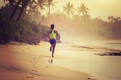 Fonctionnement de femme sur la plage tropicale pendant le lever de soleil image stock