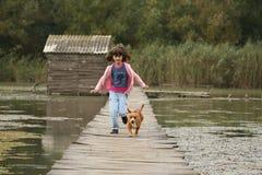 Fonctionnement de fille et de chien Image stock