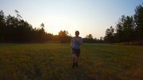 Fonctionnement de fille sur l'herbe de pré au coucher du soleil banque de vidéos
