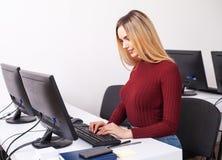 Fonctionnement de jeune femme et programmation sur l'ordinateur dans le bureau photo libre de droits