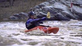 Fonctionnement de la rivière dangereuse de montagne dans un kayak banque de vidéos