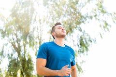 Fonctionnement de pratique focalisé de coureur en parc sur Sunny Day image stock