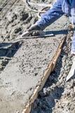 Fonctionnement de travailleur de la construction de piscine avec le flotteur en bois sur le b?ton humide image libre de droits