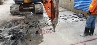 Fonctionnement de voiture de forage de roche à faire la démolition concrète avec le travailleur dans le site au train de ciel de  photographie stock