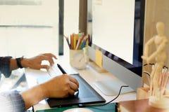 Fonctionnement et écriture de concepteur avec le carnet, ordinateur de bureau au bureau Images libres de droits
