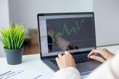 Fonctionnement et analyse d'homme d'affaires sur l'ordinateur portable avec le graphique financier photographie stock