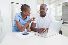 Fonctionnement heureux de couples et ordinateur portable d'utilisation Photographie stock libre de droits