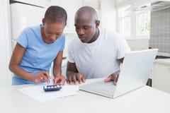 Fonctionnement heureux de couples et ordinateur portable d'utilisation Image stock