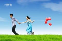 Fonctionnement heureux de couples tout en retenant la main Photographie stock libre de droits