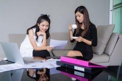 Fonctionnement heureux de deux jeune femmes d'affaires ainsi que l'ordinateur portable dans le bureau photos stock