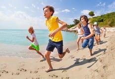 Fonctionnement le long du groupe d'eau de mer d'enfants photos stock