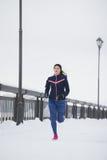 Fonctionnement modèle de forme physique de jeune femme au parc d'hiver de neige, espadrilles roses Photo libre de droits