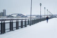 Fonctionnement modèle de forme physique de jeune femme au parc d'hiver de neige, espadrilles roses - grandes-angulaires Image stock