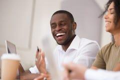 Fonctionnement parlant riant d'homme d'affaires africain heureux ainsi que les collègues amicaux images stock