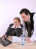 Fonctionnement pour deux personnes sur l'ordinateur portatif au bureau Image stock