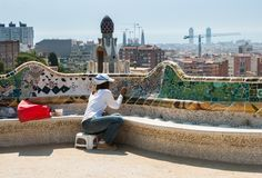 Fonctionnement professionnel de restaurateur au banc en céramique coloré dans Parc Guell Barcelone l'espagne image stock