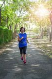 Fonctionnement pulsant heureux de femme asiatique supérieure en parc photographie stock libre de droits