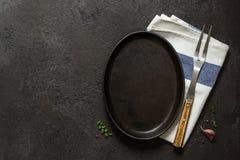 Fond à cuire foncé Plat, serviette et fourchette vides de fonte image libre de droits